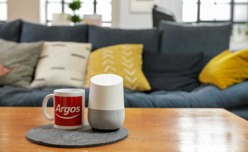 Argos logo on mug next to Google Home smart speaker