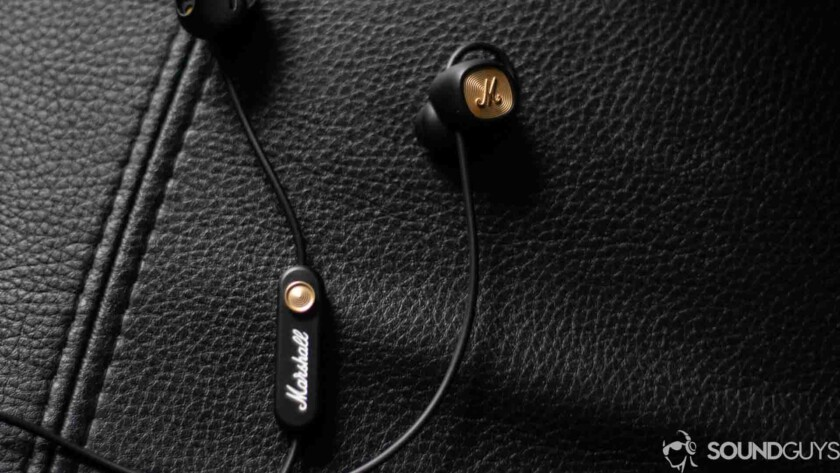 Marshall Minor II wireless earbuds in black on leather surface.