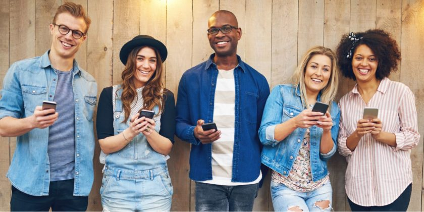 Cheerful friends standing with phones
