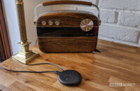 The Echo Input on a wooden desk with a speaker behind it.