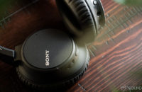 Sony WH-CH700N headphones on a cherry wood surface.