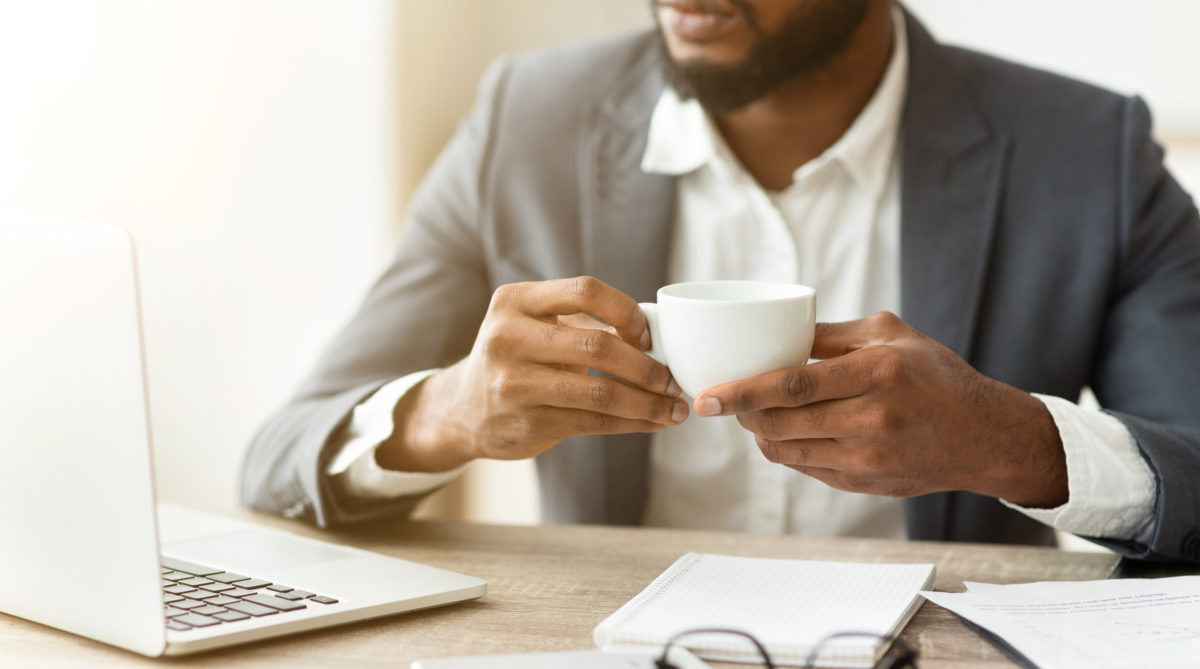 pensive businessman drinking coffee at workplace