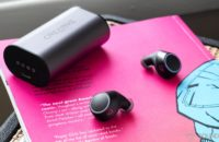 The Creative Outlier Air earbuds on a pink comic book with the charging case in the background.