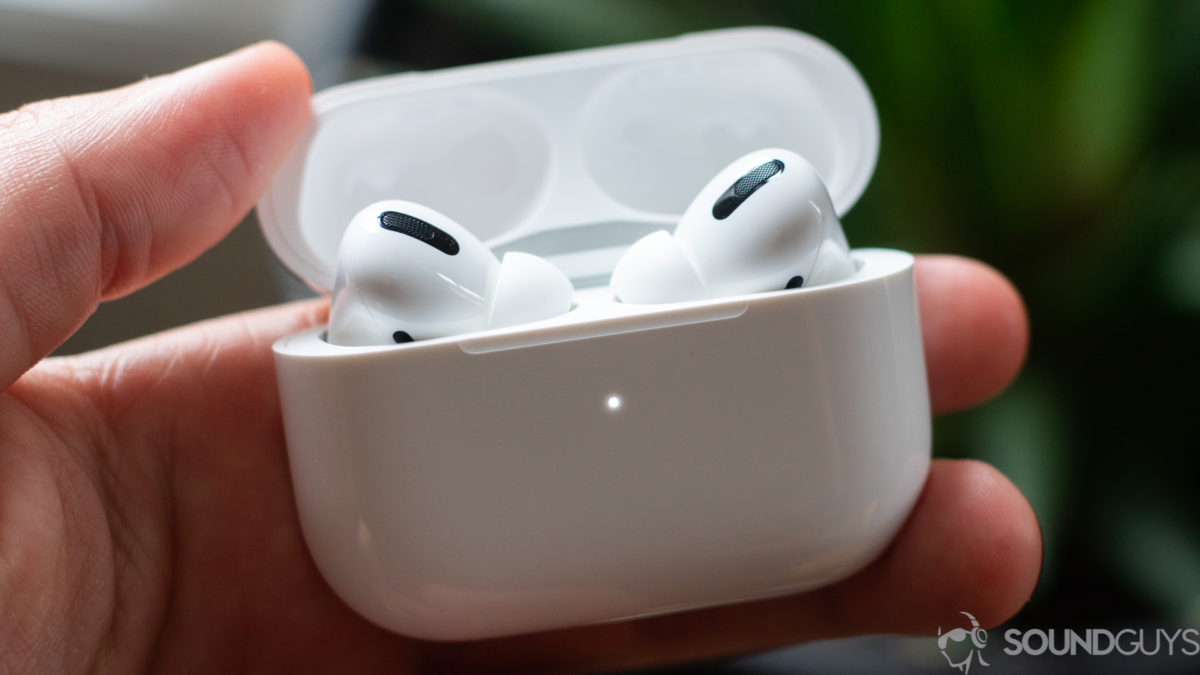 A picture of the Apple AirPods Pro earbuds charging case in a man's hand.