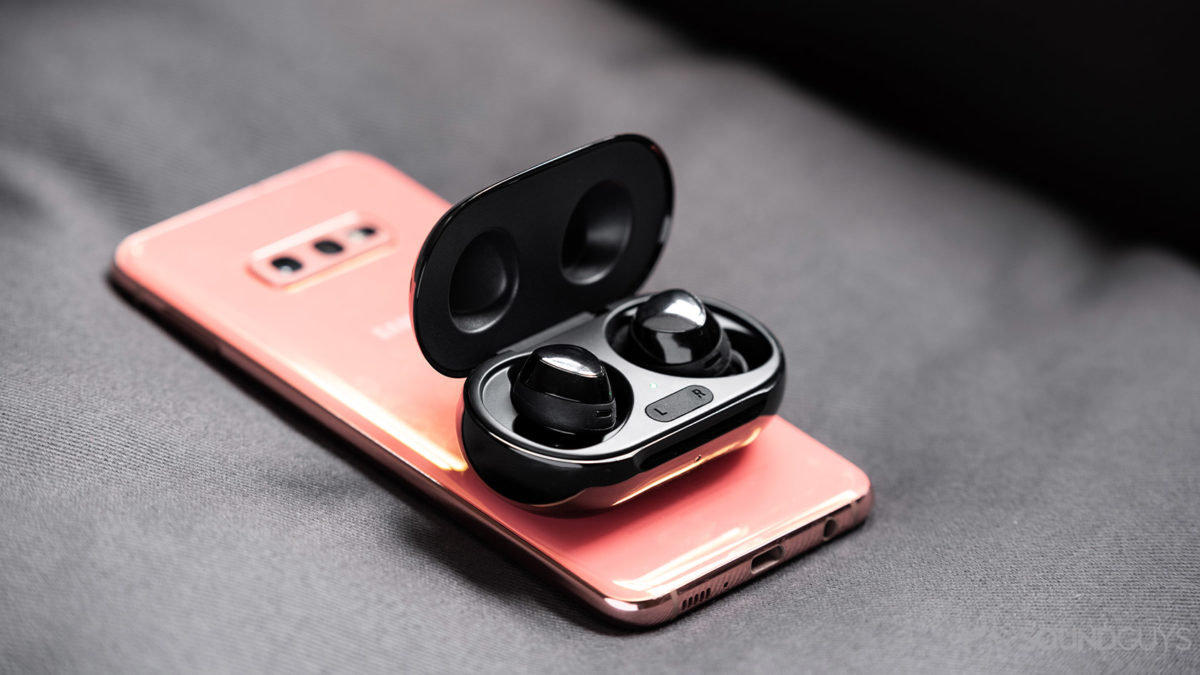 A photo of the Samsung Galaxy Buds Plus true wireless earbuds using wireless PowerShare atop a Samsung Galaxy S10e.